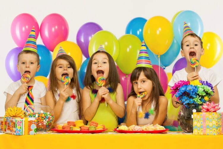 crianças na frente de mesa de festa infantil
