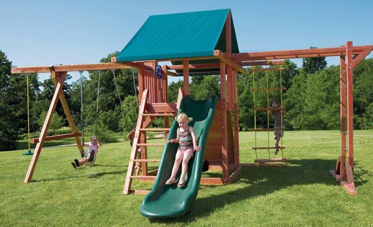crianças brincando em um playground de madeira