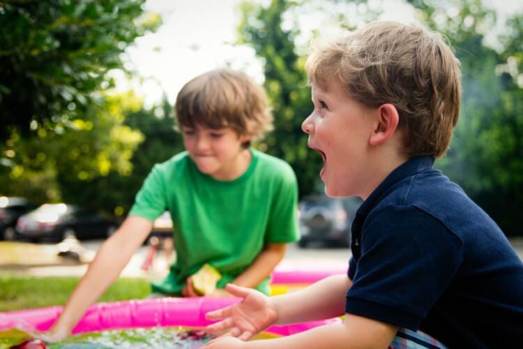 Menino brincando em piscina infantil de plástico