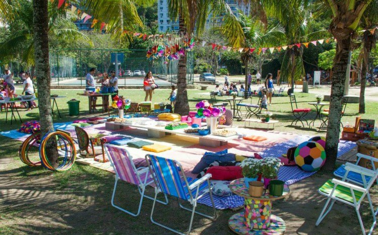 Ambiente em parque decorado para festa de aniversário com bandeirinhas, toalhas e itens coloridos.
