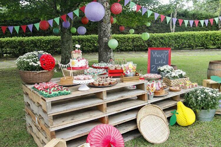 Peças de pallet sendo utilizadas como mesa para comidas de festa de aniversário