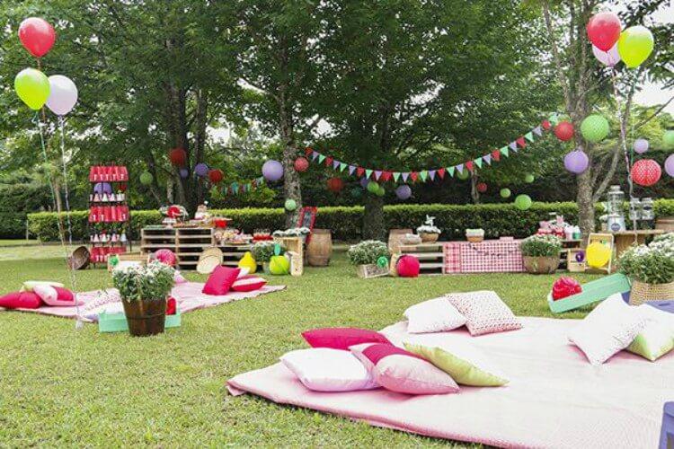 Almofadas e toalhas no chão em ambiente aberto, preparado para receber festa de aniversário.