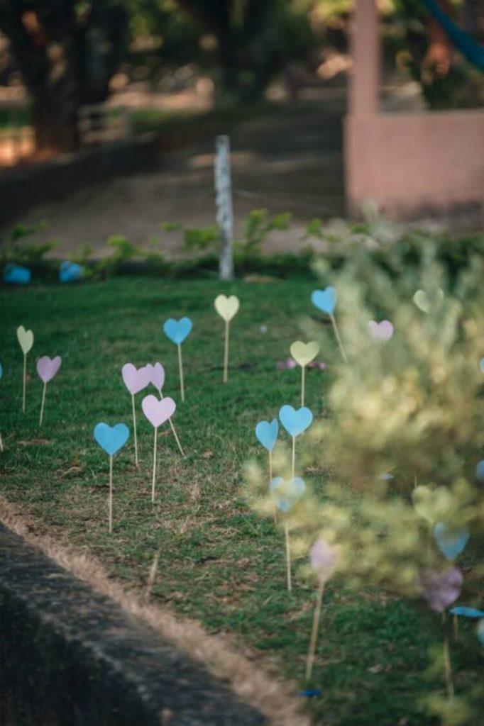 Corações de papel em palitos de madeira fincados em grama.