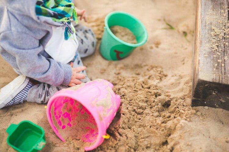 Criança brincando em tanque de areia de parquinho