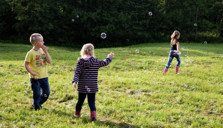 crianças brincando com bolhas no jardim