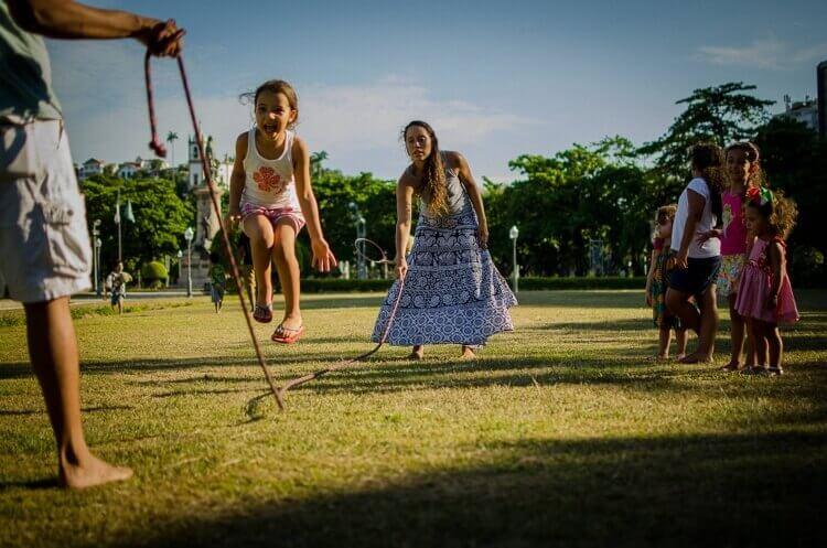 Criança feliz pulando corda segurada por uma mulher e por um homem em um parque