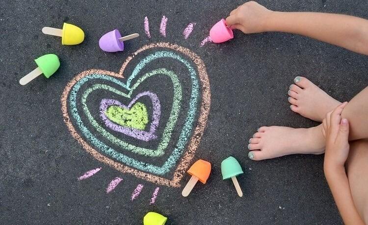Crianças desenhando no chão.