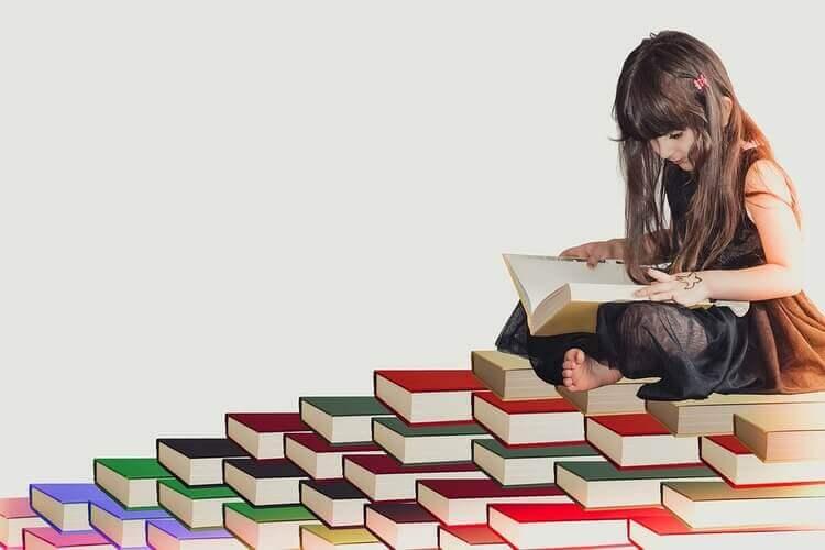 Menina sentada em cima de livros e lendo um livro.