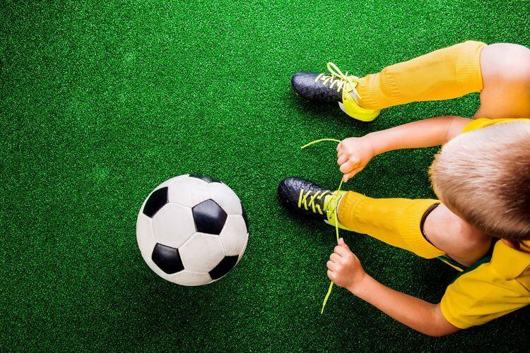 Criança amarrando chuteira de futebol