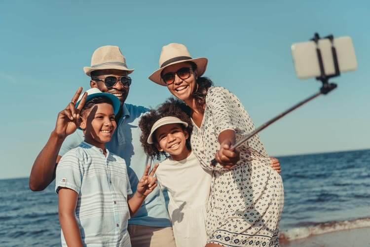 Viagem com a família na praia que está tirando um self