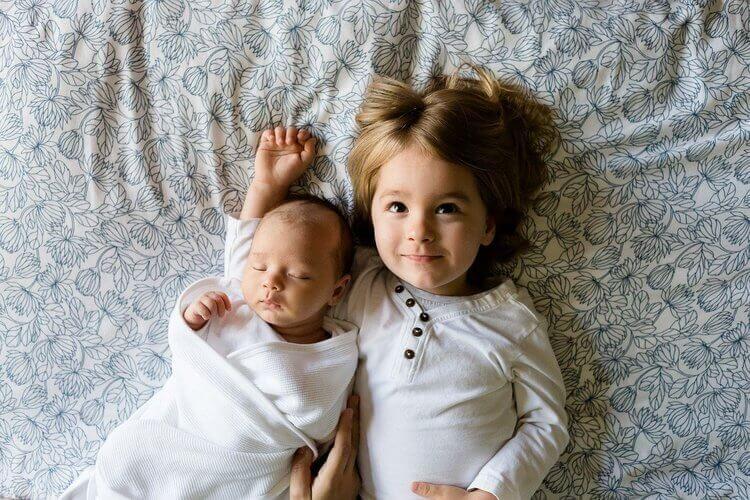Irmãos abraçados e deitados na cama