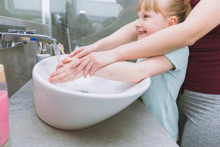 Mãe ajudando criança a lavar as mãos