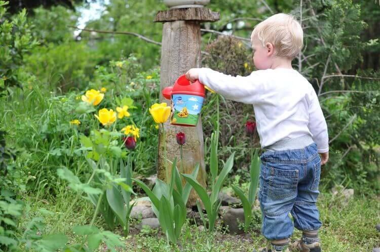 Bebê regando plantas em jardim