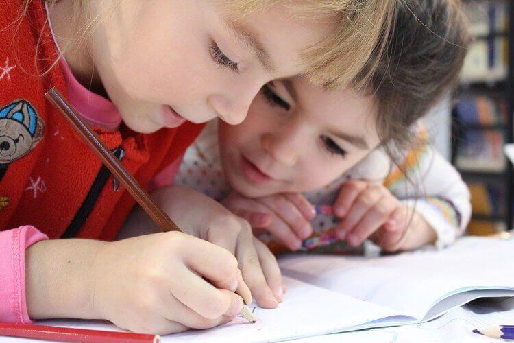 Crianças escrevendo em caderno escolar